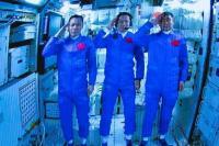 Dalam foto yang dirilis oleh Xinhua News Agency ini, para astronot China memberi hormat setelah berhasil memasuki modul stasiun ruang angkasa Tianhe saat ditampilkan di layar lebar di Beijing Aerospace Control Center di Beijing, pada 17 Juni 2021. (Foto: Jin Liwang/Xinhua) melalui AP)