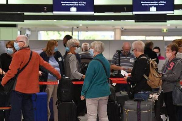 Penumpang menunggu di konter check-in untuk penerbangan Selandia Baru di Bandara Internasional Sydney pada 19 April 2021, ketika Australia dan Selandia Baru membuka gelembung perjalanan bebas karantina trans-Tasman.  (AFP/Saeed Khan)