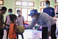 Salah seorang staf Plan Indonesia memberikan bantuan sebuah bola kepada anak korban bencana badai Seroja di Lembata.